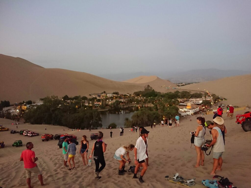Evening vibe by the oasis on the tourist route. Huacachina Oasis, Peru.